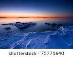 This is photographed after sunrise in the coast of Uutela, Helsinki. There is  ice in foreground and open water with ice float in background. - stock photo