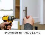 Stock photo the worker sets a new handle on the white cabinet with a screwdriver installing kitchen cabinets 757913743