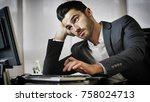 Stock photo tired bored young businessman sitting at his desk in front of his computer with his chin resting on 758024713