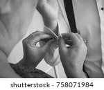 Small photo of Godmother helping groom to get dressed. Preparations. Black and white shot. Unrecognizable people.