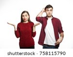 Small photo of Confused young female wearing cozy sweater shrugging shoulders and gesturing with open palms, feeling uncertain about making serious decision, posing in studio together with her indecisive husband