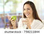 happy woman holding an apple... | Shutterstock . vector #758211844