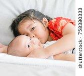 little sister hugging her baby... | Shutterstock . vector #758380333