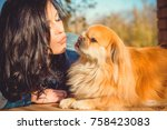 Stock photo pretty brunette hair young woman on a walk with friend little nice red dog pekingese lady of dog 758423083