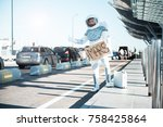 """Small photo of Spaceman wearing strange armor is asking for a ride, holding a cardboard sign with the word """"Mars"""" written on it. Full length portrait. Copy space on left side."""