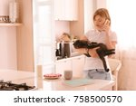 Stock photo young woman playing with her cute cat in home blonde girl holding her pretty kitten and talking on 758500570