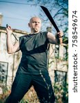 Small photo of Two machete fighting concept. Long knife weapon training. Demonstration with a real metal machete