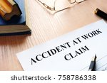 Small photo of Accident at work claim and glasses on a table.