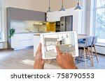 Stock photo hands holding tablet with kitchen interior sketch in background real finished kitchen interior 758790553