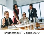 Small photo of Female executive pointing at a paper on table and putting her ideas during meeting . Group of corporate professionals having meeting in a board room.