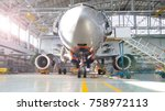 Stock photo airplane in hangar front view of aircraft and light from windows 758972113