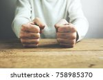 man fists clenched on a wooden... | Shutterstock . vector #758985370