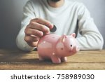 Small photo of Man putting coin in piggy bank. Saving money concept