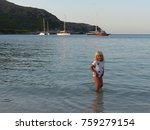 Small photo of Agulla beach, Majorca / Spain - August 2017: little girl playing in the waters of Agulla beach