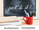 Stock photo lettering of phrase just do it on black chalkboard on a background of notepads and diary and a red 759320590