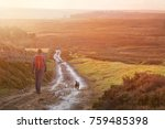 Stock photo a hiker and their dog walking along a wet dirt track at sunset in the english countryside 759485398