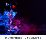 Stock photo martini cocktail splashing in blue and purple smoky background 759683956