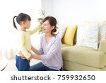 mother tieing child's hair... | Shutterstock . vector #759932650