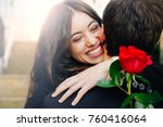 Stock photo beautiful and happy young woman in love hugging her boyfriend holding a red rose 760416064