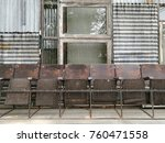 Small photo of Many old brown wooden chairs are stand abreast on plank in front of curly piece of wall and window