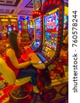 Small photo of Las Vegas, United States of America - May 06, 2016: Concentrated girl playing slot machines in the Excalibur Hotel