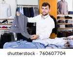 young smiling man choise new... | Shutterstock . vector #760607704