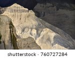 Small photo of A rock, a cliff of yellowish color with an acute-angled peak among the dark mountains.