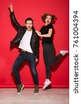 Small photo of Full length image of carefree screaming punk couple posing and looking at the camera over red background