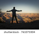 Silhouette of a man from the rear standing with outstretched arms on the rim at a viewpoint overlooking the Grand Canyon, Arizona with dark vignette
