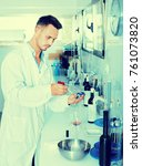 Small photo of Young man in white coat checking wine acidity and sugar saturation in chemical laboratory on winery