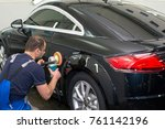A man polishes a black car with a polisher - stock photo