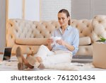 Small photo of Tears. Unhappy young emotional woman sitting on the floor and crying while tearing and scratching a piece of paper
