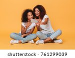 Small photo of Portrait of a two joyful afro american sisters taking a selfie while sitting and showing peace gesture isolated over orange background