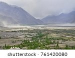 Small photo of Sandstorm in a wide wide mountain valley: in the foreground there are magnificent expanses with a river, green trees and white Buddhist stupas, in the distance the bluish mountains with whirlwinds.