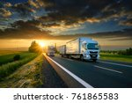 Overtaking trucks on an asphalt road in a rural landscape at sunset