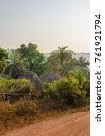 Small photo of Traditional thatched round huts of Guinea hidden among trees and palms at gravel road during sunset, West Africa