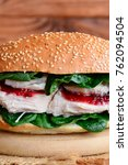 Small photo of Chicken fillet burger. Easy chicken fillet burger with spinach and berry jam on a wooden board. Vertical photo. Closeup