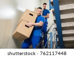 two young male movers in blue... | Shutterstock . vector #762117448