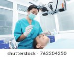 a female dentist is treating a... | Shutterstock . vector #762204250