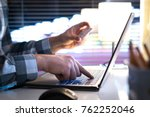Online shopping and paying with credit card and laptop. Man buying on an internet store in modern home office late at night. Typing login information, pin code and password. - stock photo