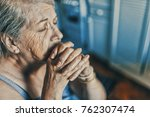 a worried senior woman at home... | Shutterstock . vector #762307474