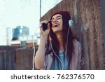 young urban woman listens to... | Shutterstock . vector #762376570
