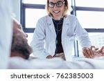 Happy Female Doctor Examining...