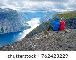 couple sits on rock and looks... | Shutterstock . vector #762423229