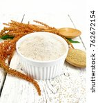 Small photo of Flour amaranth in a bowl, a spoon with grain, brown flower with green leaves on the background light wooden boards
