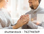Small photo of Amorous guy holding hands of his girlfriend and talking about his feelings