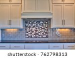 Stock photo modern kitchen with cooktop black granite counter tops white cabinets and gray subway tile 762798313