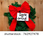 Small photo of A big red Christmas bow over a green Christmas tree branch and Santa is coming text on a note on wooden table