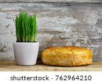 Small photo of Homemade decorated Serbian slava bread and young wheat in pots on the rustic wooden board.