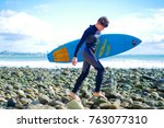 male surfer carry blue short... | Shutterstock . vector #763077310